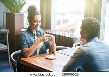 Cheerful young man and woman are drinking coffee in cafe. They are talking and flirting. The couple is smiling happily
