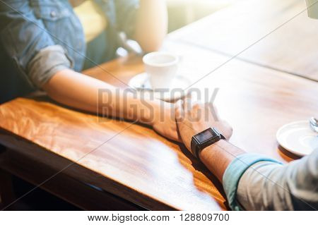 Close up of arms of young loving couple holding hands with romance. They are sitting at table in cafe