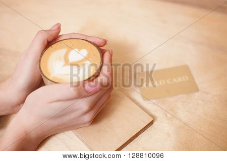 Close up of female hands holding a cup of hot coffee. Gold card on the table