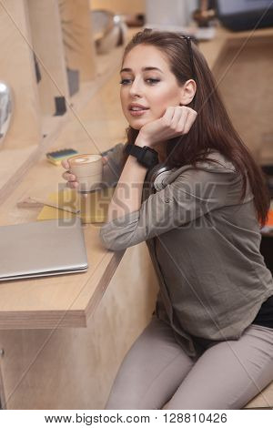 Beautiful young woman is enjoying hot latter. She is dreaming and smiling. The lady is sitting at desk