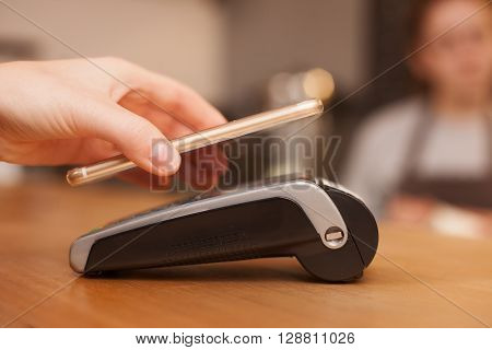 Close up of female hand. Woman is using a mobile phone to pay in shop