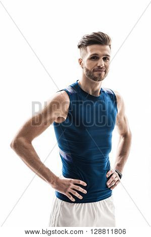 I like sport. Waist up portrait of handsome strong athlete smiling and looking at camera happily. Man is standing with arms akimbo. Isolated