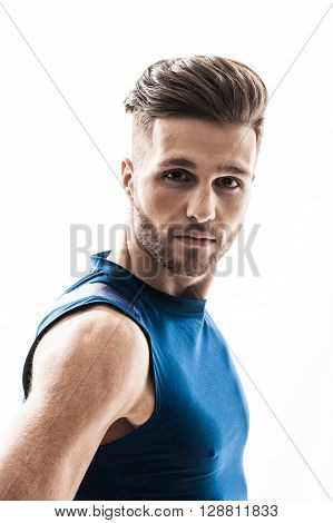 Waist up portrait of confident sportsman looking at camera with seriousness. He is standing and posing. Isolated