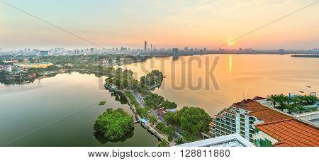 Hanoi, Vietnam, September 28, 2015: Panorama West lake sunset when sun go down horizon where skyscrapers, still lake, green path through small island creates beauty idyllic watching in Hanoi, Vietnam