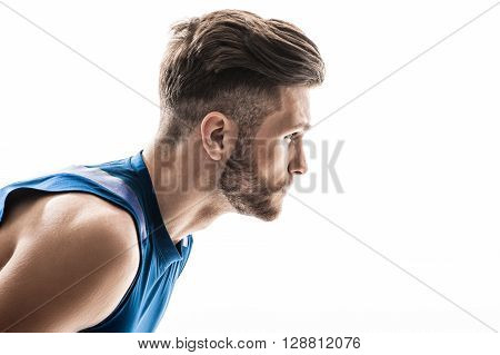 Portrait of handsome young jogger preparing for running. He is standing and posing. The man is looking forward with aspiration. Isolated and copy space in right side