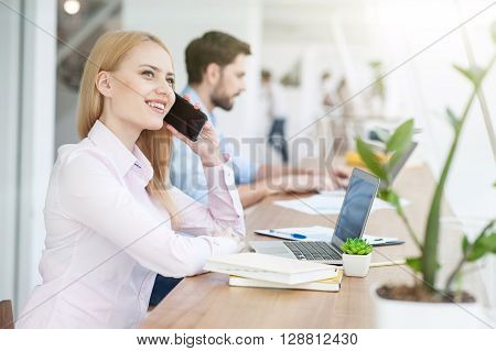 Cheerful young woman is talking on mobile phone. She is sitting at table in office and smiling. Her male colleagues is typing on laptop on background