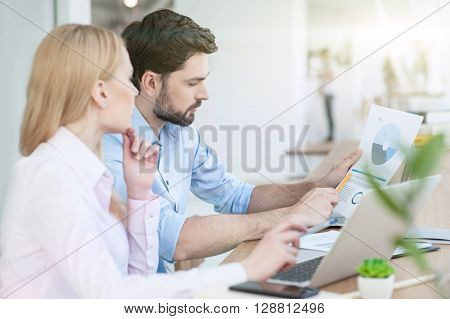 Skillful young two colleagues are working together. Man is holding a document and explaining his idea. Woman is sitting at desk and listening to him attentively