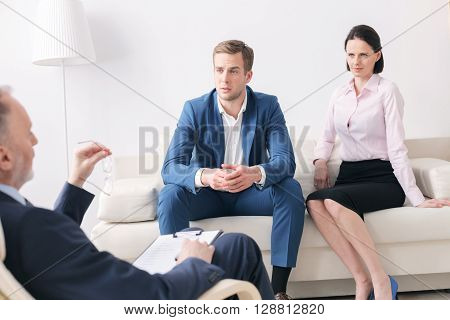 Young married couple is consulting the psychologist. The doctor is explaining them something. They are sitting on sofa and listening to him attentively