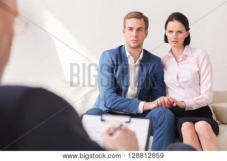 Young married couple is sharing their problems with psychologist. They are sitting on couch and looking at doctor with seriousness. The practitioner is writing with concentration