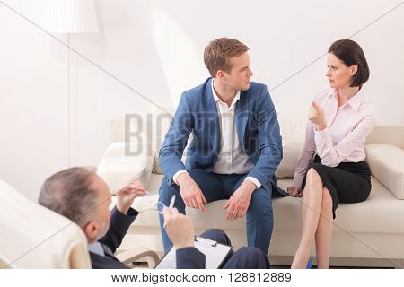 The doctor is right. Young family is solving their problems in psychotherapist. The woman is pointing finger at practitioner pensively. Her husband is looking at her seriously