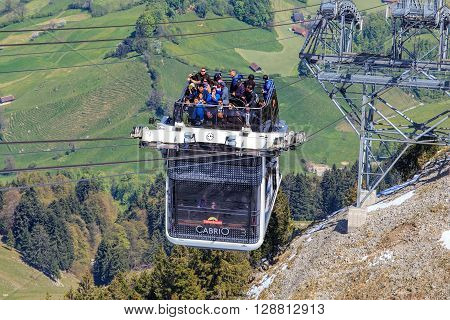 Mt. Stansenhorn, Switzerland - 7 May, 2016: people in a gondola of the Stansenhorn Cabrio cable car approaching the station on the top of the mountain. Stansenhorn Cabrio is the the world's first double deck open top cable car.