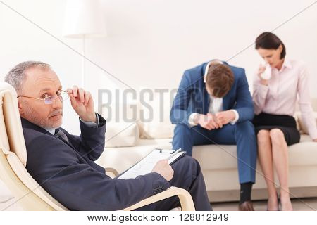 Married couple is visiting a psychotherapist. Woman is crying. Man is hanging his head with frustration. The doctor is sitting and looking at camera seriously