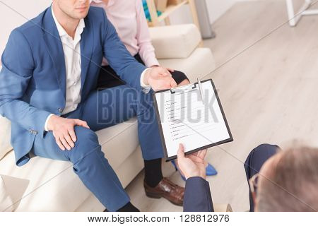 Professional psychologist is asking a married couple to fill in the psychology questionnaire. He is giving to the man a document