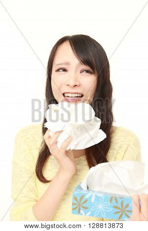 young woman with an allergy sneezing into tissue