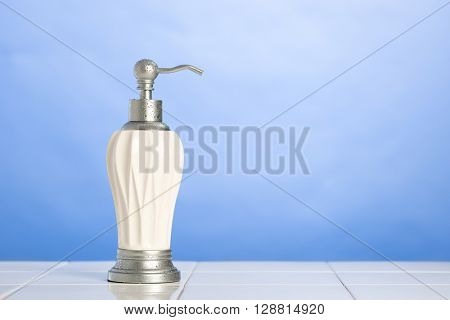 Soap dispenser on tiled ledge with fresh blue background - plenty of copy space