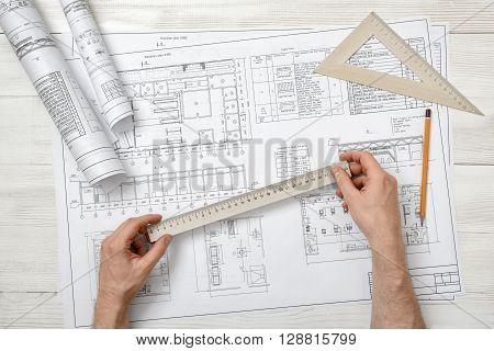 Close-up hands of architect while working process with centimeter ruler. Workplace of architect. Engineering work. Construction and architecture. Architect drawing. Measurement.