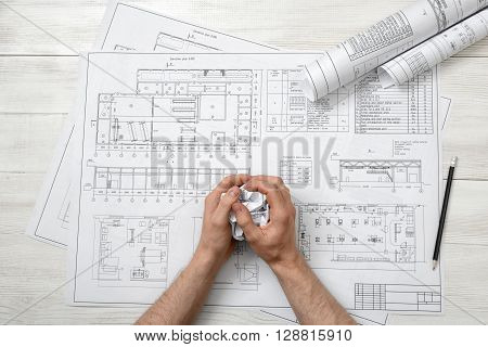 Closeup masculine hand with hand-folding a piece of paper. Top view composition. Anger sign. Worry process. Workplace of architect or constructor. Engineering work. Construction and architecture. Architect drawing. Draft.