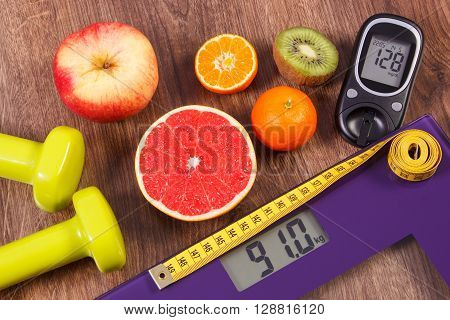 Electronic bathroom scale and glucose meter with result of measurement weight and sugar level healthy food and dumbbells for fitness concept of healthy lifestyles diabetes and slimming