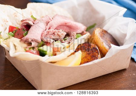 food truck meal of lamb wrap with roasted potato shawarma style with hummus