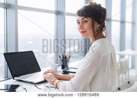 Young female office employee using laptop at work, smiling, looking at camera. Businesswoman typing, blogging during working day