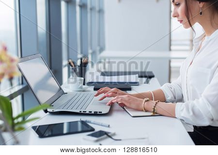 Attractive female assistant working, typing, using portable computer, concentrated, looking at the monitor. Office worker reading business e-mail