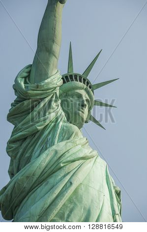 Majestic iconic lady liberty statue of liberty in New York harbor welcoming new arrivals vertical tall format orientation