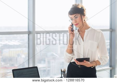 Young female assistant answering business call, holding pda, discussing work details on the cellphone