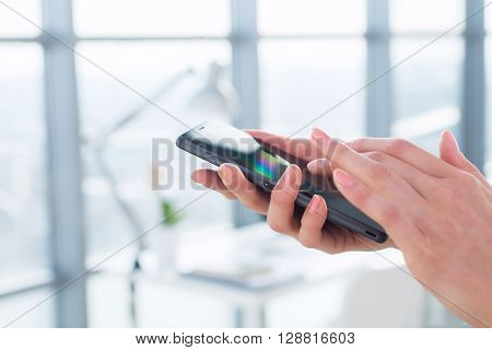 Close-up side view picture of female hands holding smartphone, using apps and wi-fi internet, reading messages