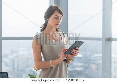 Close-up portrait of a young attractive freelancer using tablet for telework, typing and reading new messages on-line