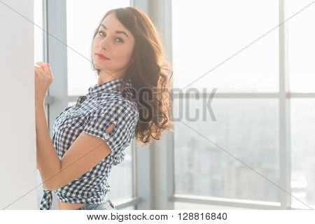 Beautiful woman with long loose hair standing next to wall in spacious light room, posing, looking at camera