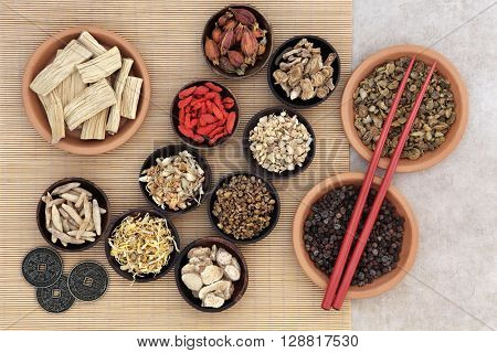 Traditional chinese herbal medicine with herb selection, i ching coins and chopsticks over bamboo background.