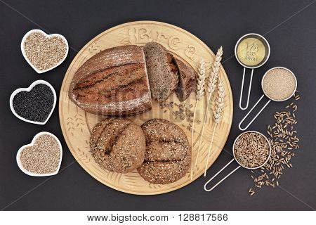Homemade rye bread loaf and seeded rolls on a wooden board  with oatmeal, poppy and sesame seed in heart shaped bowls and olive oil, yeast and rye grain in measuring scoops.