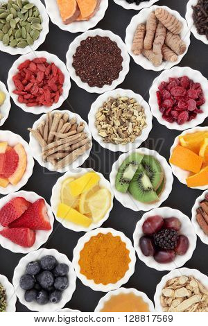 Super food and medicinal herb selection for cold and flu remedy including foods high in antioxidants and vitamin c over grey background.