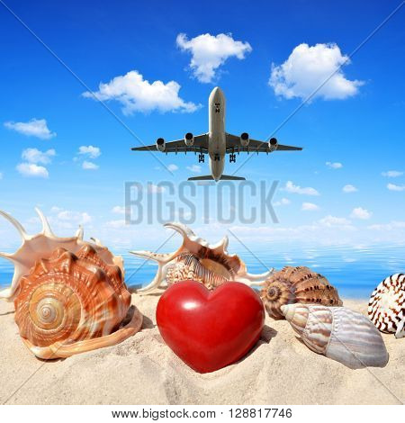 Landing an aircraft on a tropical island. In the foreground, shells with heart in sand.