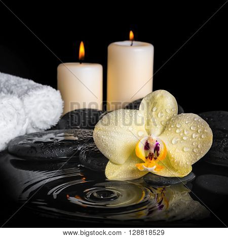spa background of yellow orchid (phalaenopsis) on zen stones drops candles and stacked of towels with ripple reflection water close up