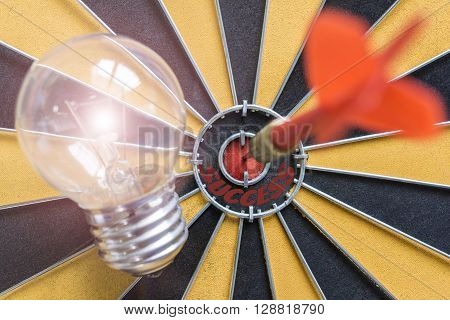Arrow hitting the success bullseye target with idea lamp on dartboard Success business finance wealth prifit  investment concept symbol of successful
