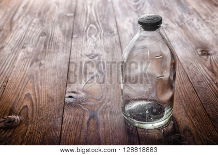 Top View Of Dirty Empty Vintage Glass Medicine Bottle With Stopper On Wooden Deck Background