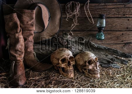 Still life with two human skulls on hay with traditional leather boots and american west rodeo brown felt cowboy hat background vintage and dark tone for horror halloween