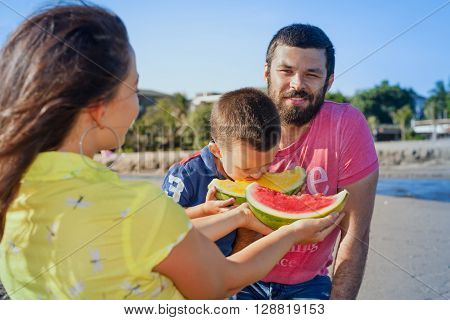 Happy family funny picnic on sea beach - mother feed baby boy adult man. Father son eat fruits with fun. Active parents lifestyle and people outdoor activity on summer vacation with child on Bali.