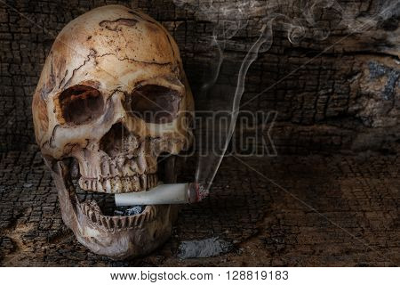 Human skull smoking cigarette with smoke on wooden background. Social issues smoking addiction concept