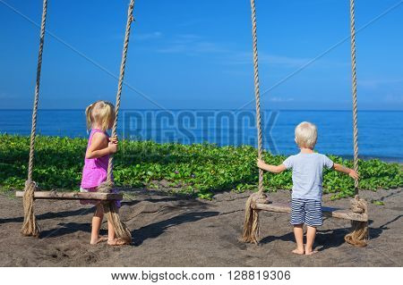 Caucasian little sibling - girl and boy have fun together on rope swing look at black sand beach sea surf on tropical island. Travel lifestyle people activity on summer family vacation with child.