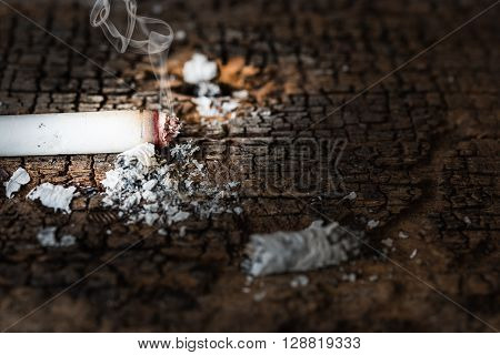 Smoking cigarette with smoke on grungy wooden. Social issues smoking addiction concept