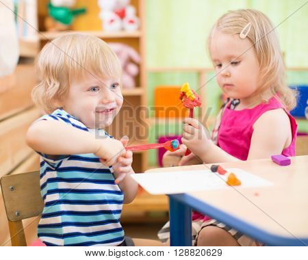 kids making arts and crafts in kindergarten with interest
