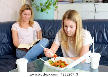 Mother Reading Abook And Daughter Eating