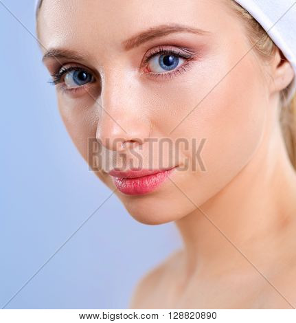 Beautiful woman with a towel on his head on a gray background.