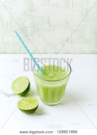 Glass of organic avocado and cucumber smoothie with lime