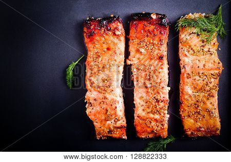 Mustard and honey glazed baked salmons fillet on black surface