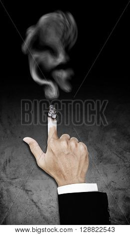 Hand with burning cigarette with smoke, concept of smoking kills