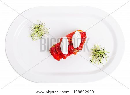 Bruschetta with stewed peppers and mascarpone cheese on plate with with microgreen herbs. Isolated on a white background.