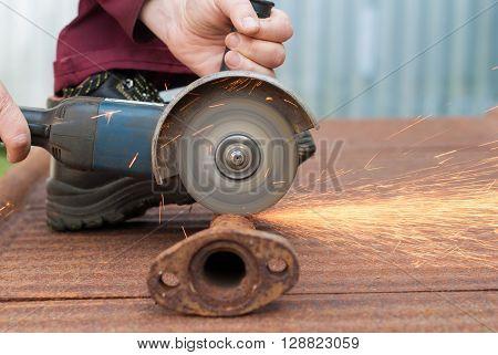 Man cuts metal electric saw close-up .